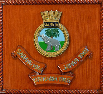 A wooden HMS Gambia crest with Battle Honours